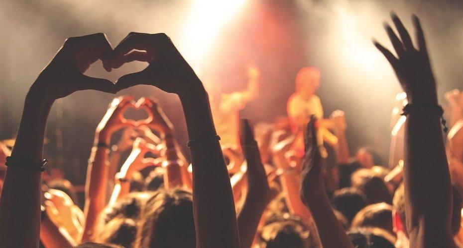 Un photo d'un concert, qui montre des mains étant formés d'un cœur.