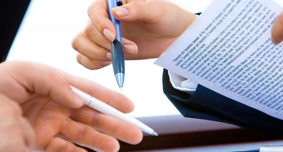 Une personne qui tient dans sa main un papier et un stylo, avec une autre personne qui se tient devant lui/elle.